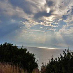 photo of sun behind the clouds, One Million Words, travel & discover mysterious Greece