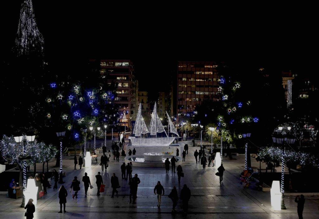 People walk past an illuminated boat, which is part of this year's Christmas decorations, at Syntagma (Constitution) square in central Athens December 11, 2013. The centrepiece of this year's Christmas light up, which is an old tradition in Athens, is a boat instead of the usual Christmas tree. REUTERS/John Kolesidis (GREECE - Tags: SOCIETY)